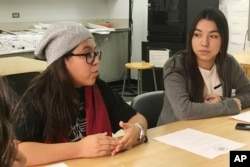 FILE - Mexican students Yatziri Tovar, left, and Roxanna Herrera, discuss their travel plans at City College of New York, Dec. 1, 2016.