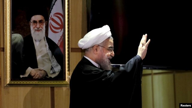 FILE - Iranian President Hassan Rouhani waves as he stands next to a portrait of Iran's Supreme Leader Ayatollah Ali Khamenei, Dec. 21, 2015.