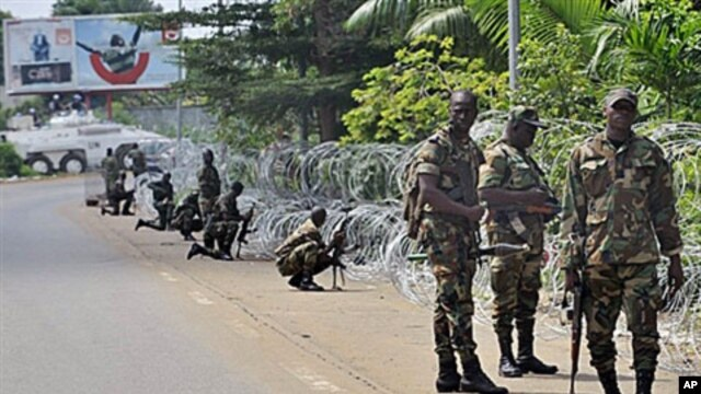 Armed members of the New Forces adopt combat positions near the hotel that houses the rival government declared by Alassane Ouattara in Abidjan, Ivory Coast, on Dec 13, 2010