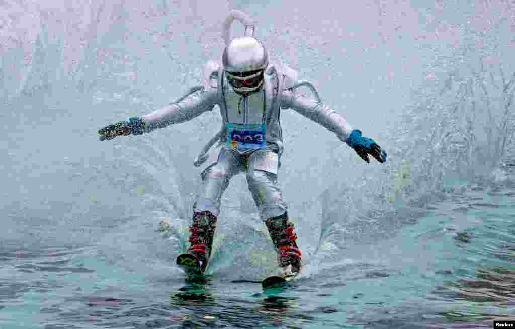 A skier in festive clothes tries to cross a pool of water at the bottom of a ski slope, while competing in the Gornoluzhnik event that marks the end of the ski season at the Bobrovy Log ski resort, in Krasnoyarsk, Russia, April 14, 2019.