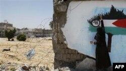 Một phụ nữ Palestine sơn graffiti cờ Palestine lên một bức tường ở Gaza City, thứ năm 6 tháng năm, 2010
