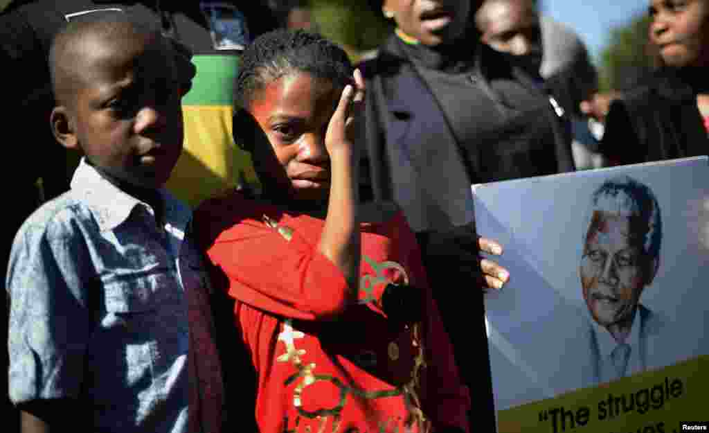 A girl weeps as she stands next to a portrait of Nelson Mandela held by ANC supporters outside the Mediclinic Heart Hospital in Pretoria, South Africa, June 28, 2013.