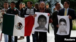 Demonstrators hold Mexican flags and portraits during a protest in support of 43 missing students of the Ayotzinapa teacher training college Raul Isidro Burgos, outside the Mexican Embassy in Bogota, Nov. 7, 2014.