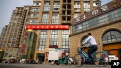 FILE - A delivery cart and cyclist ride past a building housing the Fengrui law firm in Beijing. Several lawyers from the firm have been targeted by authorities.