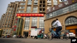 FILE - A delivery cart and cyclist ride past a building housing the Fengrui law firm in Beijing. Observers say China has shown little sign of easing its clampdown on rights defenders one year after the government arrested and interrogated nearly 320 human rights lawyers and activists.