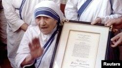 特蕾莎修女1996年11月16日在她所创办的慈善机构加尔各答总部,展示她获得的荣誉美国公民证书。