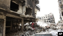 FILE - Rubble and heavy damage remain on a deserted street during a government escorted visit to Yarmouk refugee camp in Damascus, Syria, April 9, 2015. The United Nations brokered a deal to relocate some IS fighters and their families.
