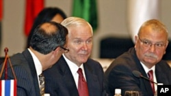 U.S. Defense Secretary Robert Gates, center, listens to his aide while attending the first Association of Southeast Asian Nations (ASEAN) Defense Ministers Meeting Plus at the National Convention Center in Hanoi, 12 Oct. 2010