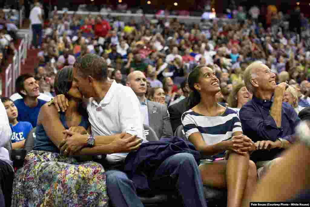 """La Première dame et le président s'embrasse devant les caméras (la """"kiss-cam"""") lors d'un match de basketball, à Washington DC, le 16 juillet 2012."""