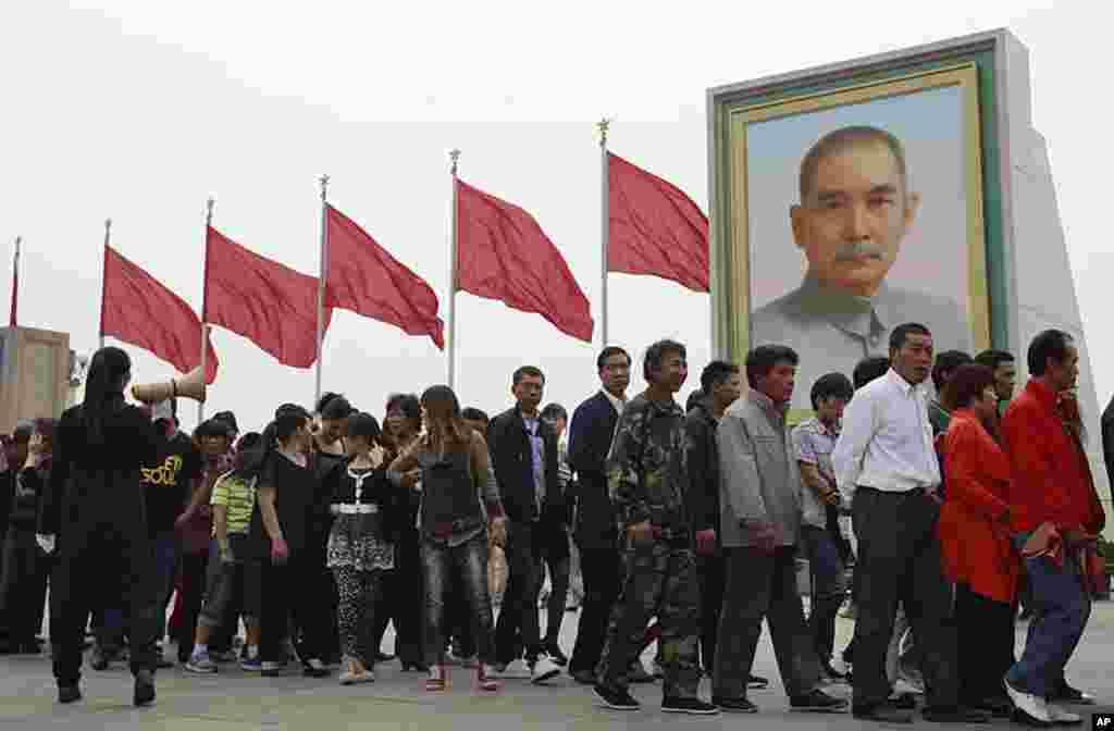 Hàng ngàn du khách đổ xô đến Quảng trường Thiên An Môn để vui hưởng Ngày Lễ Lao động, một ngày lễ công cộng. Mọi người đứng sắp hàng trước ảnh Tôn Dật Tiên để viếng xác ướp của cố lãnh tụ Trung Quốc Mao Trạch Đông, tại lăng mộ ông này ở Bắc Kinh, Trung Qu