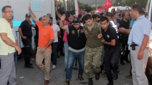 FILE - Soldiers suspected of being involved in the coup attempt are escorted by policemen as they arrive at a courthouse in the resort town of Marmaris, Turkey, July 17, 2016.