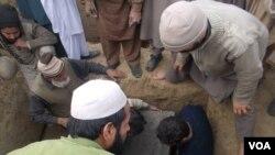 Pakistanski seljani nose jednu od žrtava Talibana u jednoj školi u Pešavaru