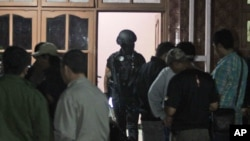 FILE - Indonesian police officers of Special Detachment 88 anti-terror unit search for evidence following a raid on a house used as a hideout by suspected militants' in Mojokerto, East Java, Indonesia, Dec. 19, 2015.