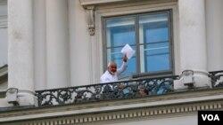 """伊朗外长扎里夫在维也纳伊核谈判地点科堡宫酒店的阳台上挥动一份文件并说:""""我们还有工作要做""""。 (2015年7月12日)"""