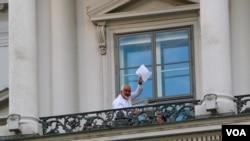 "Iranian Foreign Minister Mohamad Javad Zarif waves a document over his head, saying ""we still have work,"" on a balcony of the Palais Coburg where closed-door nuclear talks take place in Vienna, Austria, July 12, 2015. (Brian Allen/VOA)"