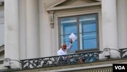 """Ngoại trưởng Iran Mohamad Javad Zarif giơ tập tài liệu và nói """"Chúng ta vẫn phải làm việc"""", trên ban công Palais Coburg ở Vienna, nơi diễn ra các cuộc đàm phán hạt nhân, ngày 12/7/2015."""