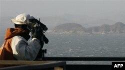 Телеоператор снимает остров Енпхендо, обстреляный северокорейской артиллерией.