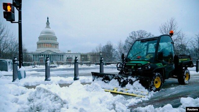 FILE - A worker clears snow from the sidewalks near the U.S. Capitol in Washington, March 17, 2014. Washington and the rest of the U.S. East Coast are expected to get a similar winter whacking this week.