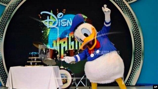 "Popular Disney charactor Donald Duck gestures to a cake as he performs on the eve of his birthday during ""Disney Magic"" event in Bangalore, June 8, 2013."