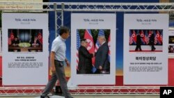 FILE - Photos of the summit between U.S. President Donald Trump and North Korean leader Kim Jong Un are displayed in Seoul, South Korea, Sept. 19, 2018.