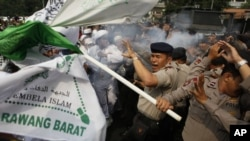 Indonesian police officers react to tear gas fired by their colleagues as they scuffle with Muslim protesters during a demonstration against American-made film 'Innocence of Muslims', September 17, 2012.