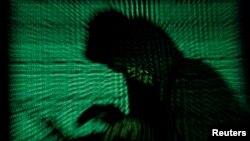 Un hombre encapuchado sostiene una computadora portátil mientras se proyecta un código cibernético sobre él en esta imagen de ilustración tomada el 13 de mayo de 2017.