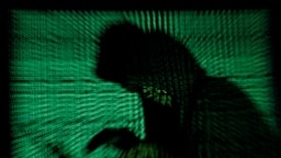 Un hacker encapuchonné tient un ordinateur portable alors qu'un cybercode est projeté sur lui. Cette photo d'illustration a été prise le 13 mai 2017. (Photo Reuters/Kacper Pempel)