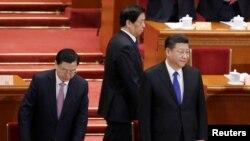 Anggota Komite Tetap Politburo (Politburo Standing Committee) Li Zhanshu (tengah) berjalan melewati Presiden China Xi Jinping (kanan) dan Ketua Komite Tetap Kongres Rakyat Nasional (NPC) pada saat mereka tiba untuk sesi pembukaan Sidang Kongres Rakyat Nasional di Aula Besar Rakyat di Beijing, China, 3 Maret 2018.