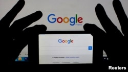FILE - A smartphone and computer screen display the Google home page.
