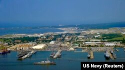 FILE - Guided missile destroyer USS Ross pulls into Naval Station Norfolk, Virginia, July 7, 2011. Eleven current or former U.S. Navy officials have been charged in a bribery investigation.