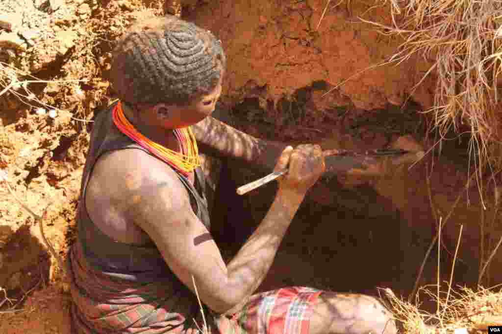 A miner uses a metal stick to loosen the dirt, which she will later mix with water and sift for gold, March 2, 2014. (Hilary Heuler for VOA)