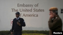A U.S. embassy security guard (L) and an Indian policeman stand in front of the main gate of the embassy as the bulldozer (unseen) removes the security barriers, in New Delhi Dec. 17, 2013.