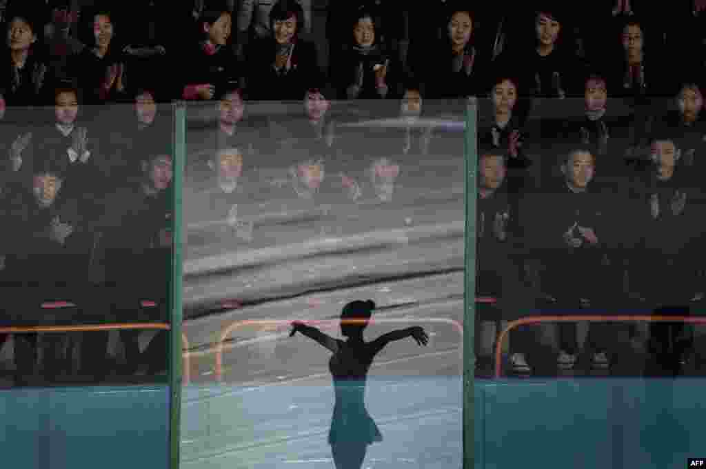 Spectators watch a figure skater performing at the Paektusan Prize International Figure Skating Festival in Pyongyang, North Korea. The festival is held annually to celebrate Kim Jong Il, the leader who oversaw the nation's first nuclear tests.