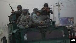 Polisi Afghanistan bergegas menuju lokasi serangan militan Taliban di pinggir kota Kabul (29/3). (AP/Anja Niedringhaus)