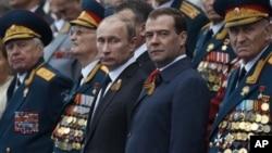 Presiden Rusia Vladimir Putin (tengah kiri) dan PM Dmitry Medvedev (tengah kanan) bersama sekelompok tentara veteran Rusia dalam parade perayaan kemerdekaan Rusia di Lapangan Merah, Moskow (9/5).