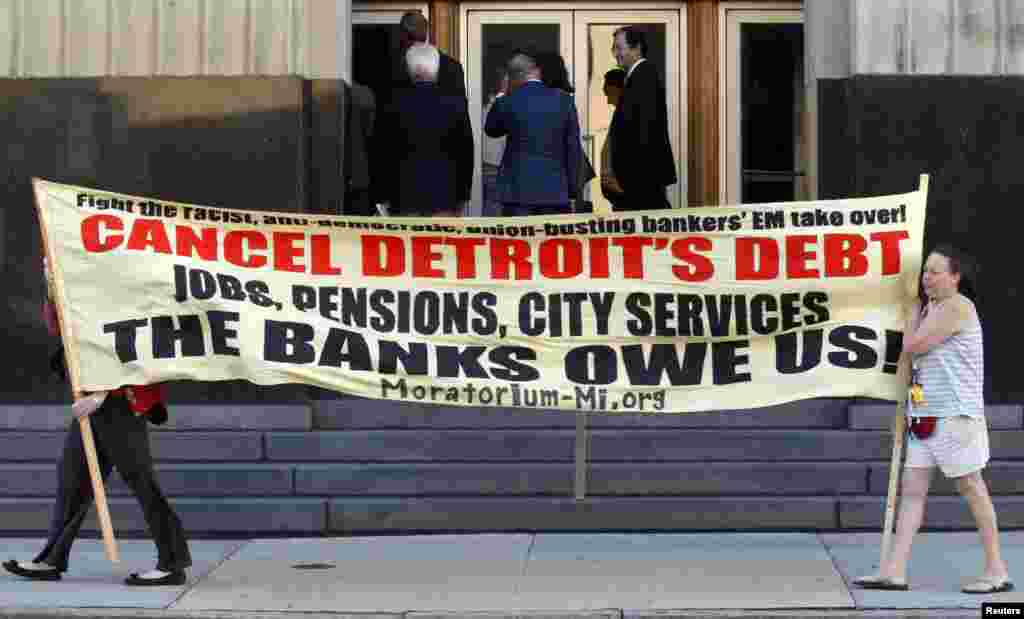 Protesters carry a banner calling for Detroit's debt to be canceled as people enter the federal courthouse for day one of Detroit's municipal bankruptcy hearings in Detroit, Michigan, USA.