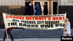 Protesters carry a banner calling for Detroit's debt to be cancelled as people enter the federal courthouse for day one of Detroit's municipal bankruptcy hearings in Detroit, Michigan July 24, 2013.