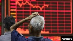 지난 27일 중국 베이징의 증권거래소에서 투자가들이 전광판을 주시하고 있다. (자료사진)