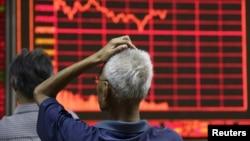 Một nhà đầu tư nhìn vào bảng điện tử hiển thị thông tin chứng khoán tại một nhà môi giới ở Bắc Kinh, ngày 27/8/2015.