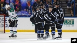 Tampa Bay Lightning's Ondrej Palat (18), of Czech Republic, is congratulated on his goal by teammates, including Tyler Johnson (9) and Nikita Kucherov (86), of Russia, as Dallas Stars' Gemel Smith reacts during the third period of an NHL hockey game, April 2, 2017.