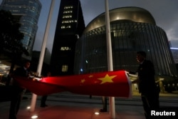 A Chinese national flag is lowered outside the Legislative Council, part of a daily ceremony in Hong Kong, Nov. 7, 2016. The day before, China's parliament passed an interpretation of Hong Kong's Basic Law saying lawmakers must swear allegiance to the city as part of China.