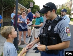 "A boy gets a ""junior"" police badge during National Night Out in Fairfax Country, Virginia, Aug. 2, 2016. (D. Block/VOA)"