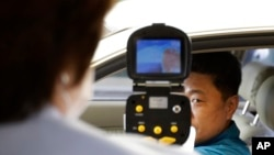 FILE - A South Korean official, left, uses a thermal camera to checks the body temperature of a driver as a precaution against Middle East Respiratory Syndrome (MERS) after he returned from Kaesong, North Korea, near Panmunjom, South Korea, June 13, 2015.