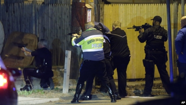 Police officers aim their weapons in Watertown, Massachusetts, April 19, 2013.