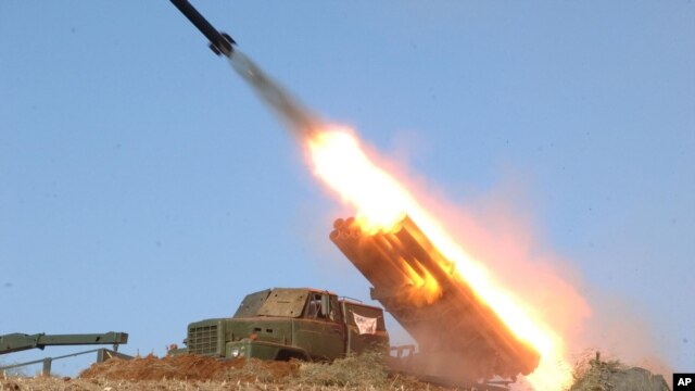 In this undated photo released by the Korean Central News Agency (KCNA) and distributed March 14, 2013,  by the Korea News Service, a rocket launcher is fired during a live drill by the Jangjae Islet Defense Detachment and the Mu Islet Hero Defense Detachment.