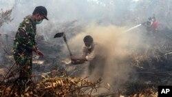 Warga dan tentara berupaya memadamkan kebakaran di sebuah lahan di Rimbo Panjang, Riau, September 2015.