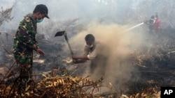 Warga desa dan anggota TNI berusaha memadamkan kebakaran hutan dan lahan di Rimbo Panjang, provinsi Riau, Minggu (6/9). Asap tebal akibat pembakaran lahan dan hutan di Pulau Sumatera dan Kalimantan semakin parah minggu ini.