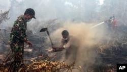 Warga desa dan petugas militer berupaya memadamkan kebakaran hutan di Rimbo Panjang, provinsi Riau, 6 September 2015 (Foto: dok).