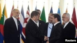 Eron prezidenti Mahmud Ahmadinejod (o'ngda) Misr prezidenti Muhammad Mursiy bilan qo'l berib ko'rishmoqda, Tehron, 30-avgust, 2012-yil.