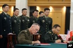 美军参联会主席邓福德上将(前左)与中国中央军委联合参谋部参谋长房峰辉在北京签署协议。 (2017年8月15日)